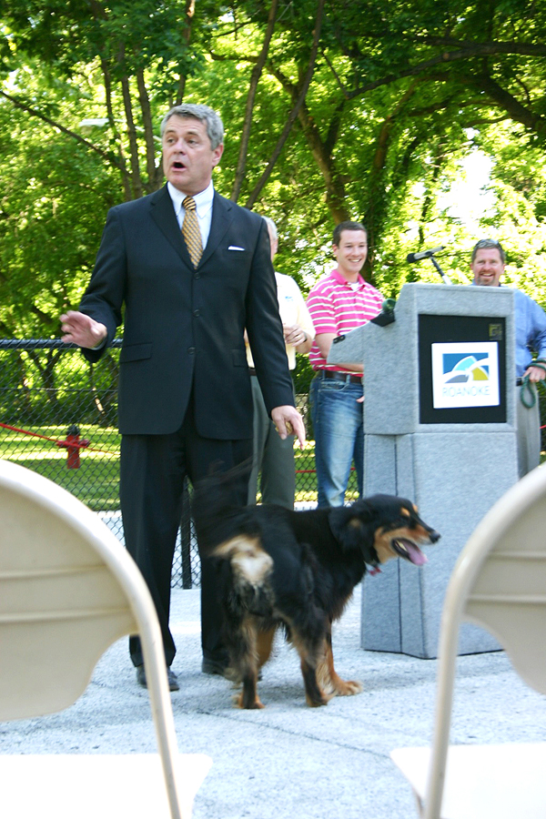 """Roanoke Mayor David Bowers with his dog """"Catcher."""" City Council members Court Rosen and David Trinkle are at the podium."""