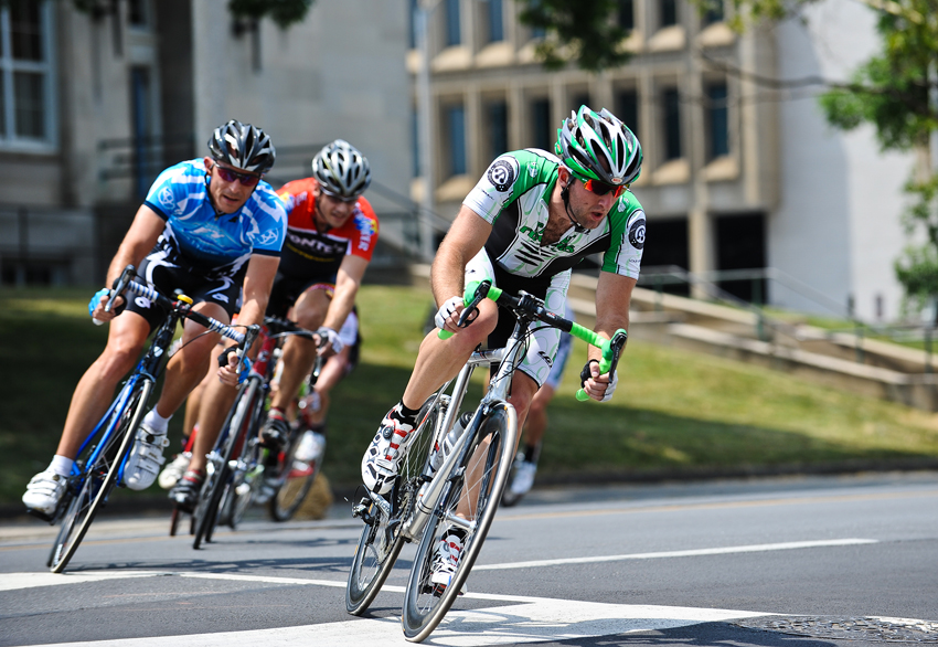 "A racer from the ""Fat Frogs"" racing team out of Virginia Beach (in green) pushes hard through the turns in front of the Noel C. Taylor Municipal Building in Downtown Roanoke last Friday. The ID3 races, in just their second year in the present format, drew more than 425 participants and substantial crowds as spectators lined the streets to watch some nationally recognized talent whiz down Roanoke avenues."