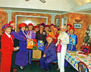 Red Hat Society members pose with a generous contribution to the SPCA.