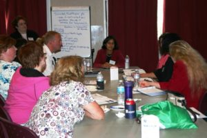 """Dr. Anjali Varma (at the head of table) leads a discussion on the benefits and challenges of """"Telemental- Health."""""""