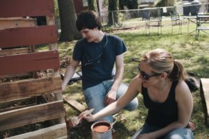 VTC students Jaclyn Dovico and Joseph Pechacek paint the new compost bins they built for the Campbell Avenue Community Garden.