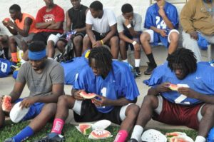 )William Fleming players (L-R) Tyrell Adams, Warren Craft and Jerome Hill enjoy the fruits of the Watermelon Ministry after their practice on Tuesday.