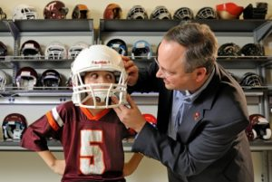 Stefan Duma, the Harry C. Wyatt Professor of Engineering, will serve for two years as interim director of the Institute for Critical Technology and Applied Science. Here Duma, an expert on concussion biomechanics and creator of the Virginia Tech Helmet Ratings, fits his son Brock with a football helmet.